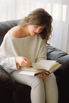 Piękna młoda kobieta czyta książkę w domu