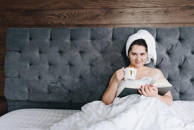 Piękna młoda kobieta czyta książkę w łóżku i pije filiżankę kawy z przestrzenią dla teksta