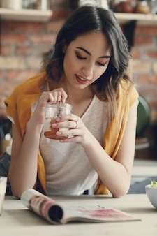 Piękna młoda kobieta czyta magazyn w domu