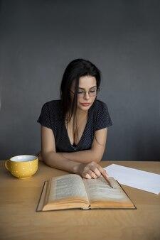 Piękna młoda kobieta czytając książkę w okularach. atrakcyjna dziewczyna studiuje przy filiżance herbaty