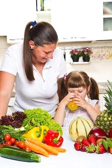 Piękna młoda kobieta daje sok pomarańczowy dziewczynka w kuchni.