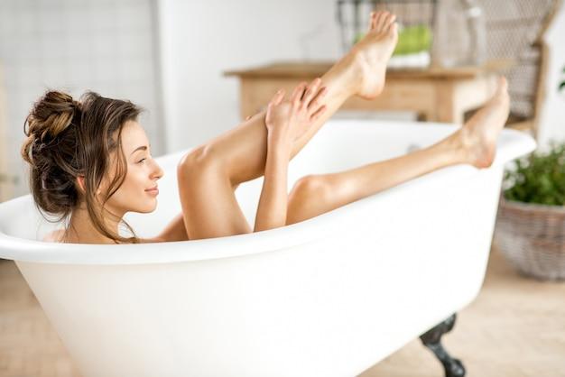 Piękna młoda kobieta dbająca o nogi leżące w wannie w łazience