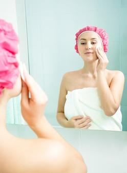 Piękna młoda kobieta demakijażu po prysznicu