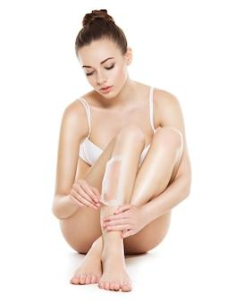 Piękna młoda kobieta depilacji nóg woskiem - studio na białym tle