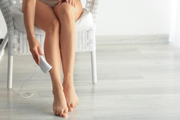 Piękna młoda kobieta depiluje nogi w domu