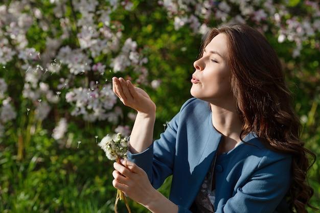 Piękna młoda kobieta dmuchanie mniszka lekarskiego w ogrodzie wiosną. ciesz się przyrodą. zdrowa uśmiechnięta dziewczyna na zewnątrz. koncepcja bez alergii. wolność