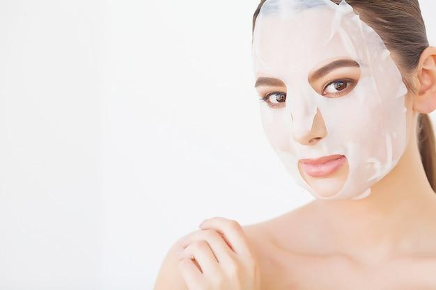Piękna młoda kobieta dostaje maskę z glinki twarzy w spa, leżąc z ogórkami na oczach