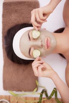 Piękna młoda kobieta dostaje twarzową maseczkę z glinki w spa, leżąc z ogórkami na oczach