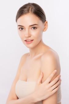 Piękna młoda kobieta dotyka jej ciało świeżą zdrową skórą, odizolowywa, piękno kosmetyki i twarzy traktowania pojęcie