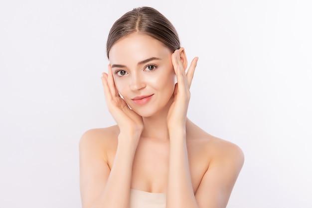 Piękna młoda kobieta dotyka jej czystą twarz świeżą zdrową skórą, odizolowywa, piękno kosmetyki i traktowania twarzy pojęcie.