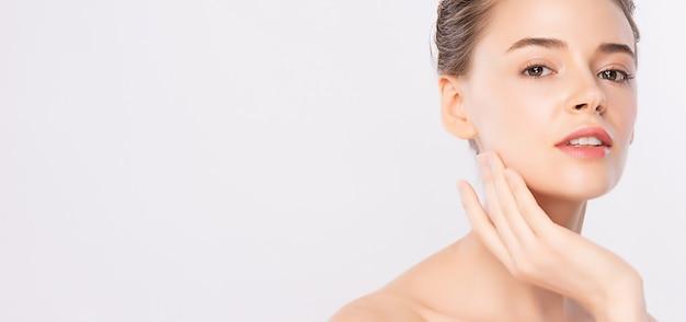 Piękna młoda kobieta dotyka jej czystą twarz świeżą zdrową skórą, odizolowywającą na bielu