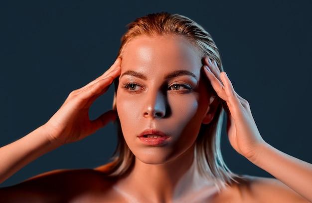 Piękna młoda kobieta dotyka własnej twarzy z czystą, świeżą skórą
