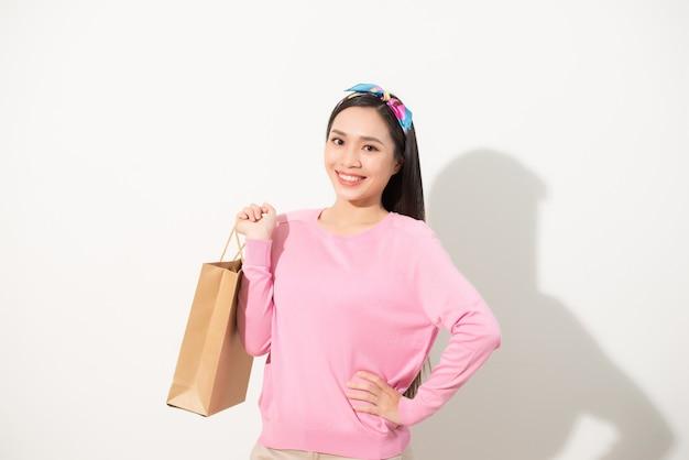Piękna młoda kobieta (dziewczyna) stojąca i trzymająca jasnobrązową torbę