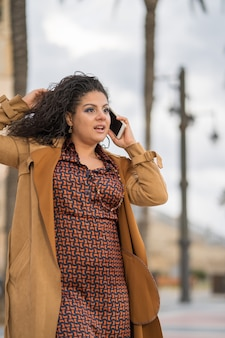 Piękna młoda kobieta dzwoni telefonem na ulicie z brąz suknią