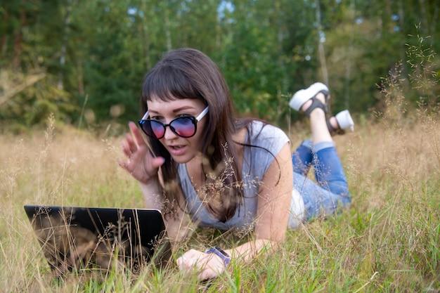Piękna młoda kobieta emocjonalnie pracuje na laptopie na słonecznym trawniku w ciepły letni dzień szczęśliwy