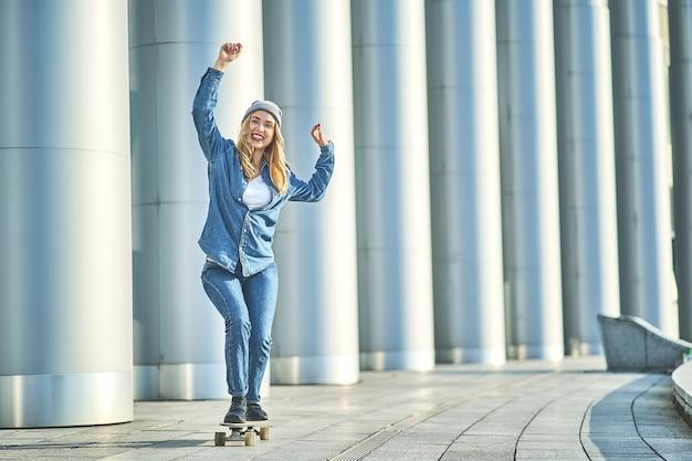 Piękna młoda kobieta figurowa, jazda na jej deskorolce w mieście