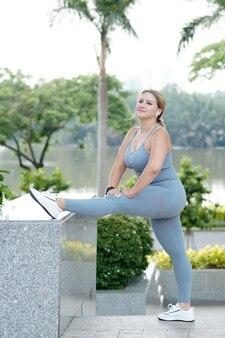 Piękna młoda kobieta fit rozciąganie nóg i trening w parku miejskim nad rzeką rano