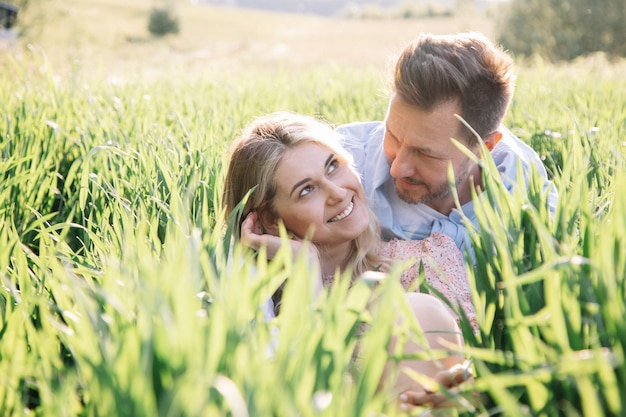 Piękna młoda kobieta flirtuje ze swoim mężczyzną siedząc na trawie, portret stylu życia