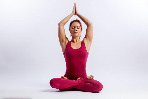 Piękna młoda kobieta gimnastyczka w obcisłe rajstopy siedzi w pozycji lotosu i uśmiechnięty