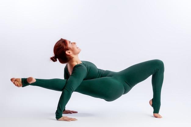 Piękna młoda kobieta gimnastyczka w obcisłych rajstopach podnosi nogę nad głowę do rozciągania i uśmiecha się na białym tle
