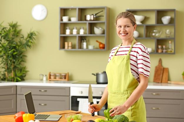 Piękna młoda kobieta gotuje w kuchni