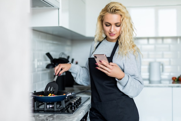 Piękna młoda kobieta gotuje zdrowego gościa restauracji używać smażyć nieckę, używać telefon komórkowego w kuchni