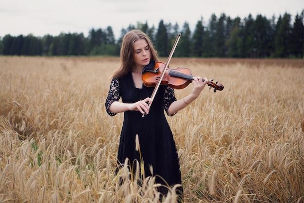 Piękna młoda kobieta gra na skrzypcach na polu dojrzewania pszenicy.