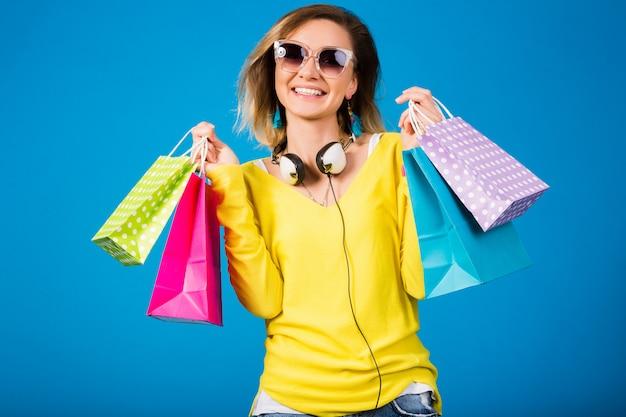 Piękna młoda kobieta hipster, trzymając kolorowe papierowe torby na zakupy