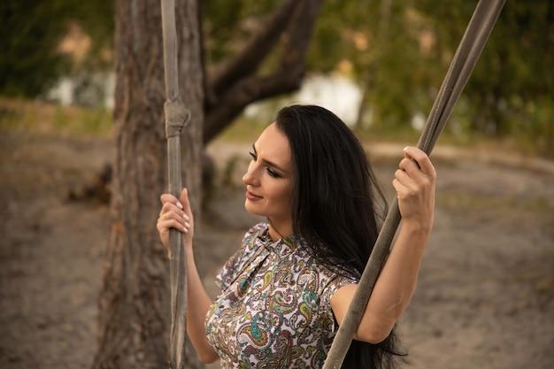 Piękna młoda kobieta huśta się i cieszy się naturą.