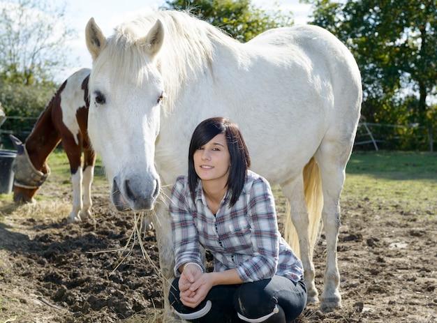 Piękna młoda kobieta i biały koń