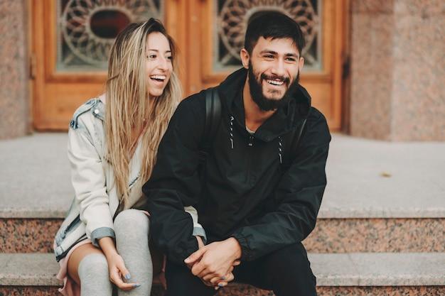 Piękna młoda kobieta i brodaty mężczyzna siedzi razem na schodach na zewnątrz i śmiejąc się radośnie