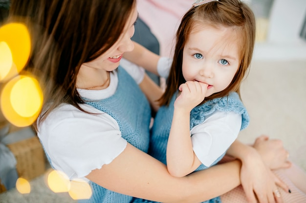 Piękna młoda kobieta i jej urocza córeczka przytulają się w tych samych strojach z uśmiechem. święta bożego narodzenia