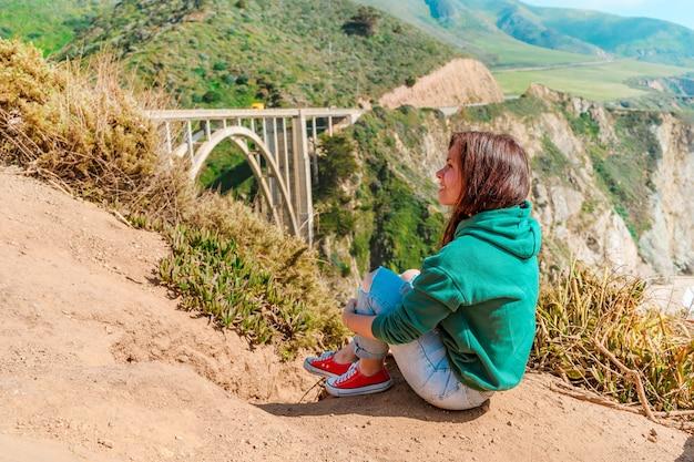 Piękna młoda kobieta i malowniczy most nad rzeką bixby na wybrzeżu big sur