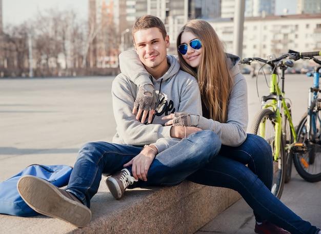 Piękna młoda kobieta i młody człowiek z rowerami w mieście