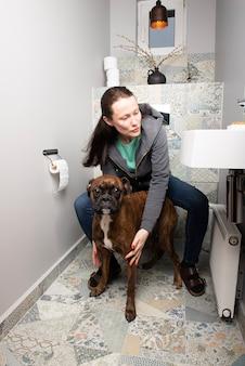 Piękna młoda kobieta i pies bokser we wnętrzu domowej toalety
