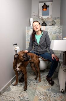 Piękna młoda kobieta i pies bokser we wnętrzu toalety domowej