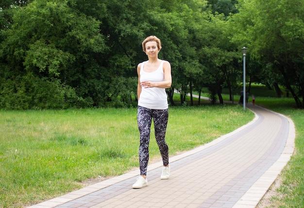 Piękna młoda kobieta idzie do sportu w parku w przyrodzie. kobieta zajmuje się fitnessem w odzieży sportowej. ładowanie. rozciąganie.
