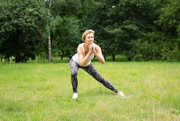 Piękna młoda kobieta idzie do sportu w parku w przyrodzie. kobieta zajmuje się fitnessem w odzieży sportowej.