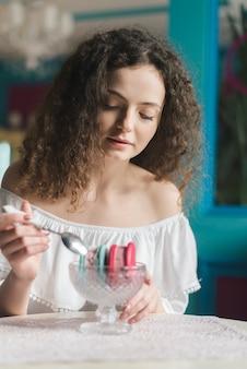 Piękna młoda kobieta je lody kanapki z łyżką