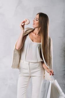 Piękna młoda kobieta je pączek