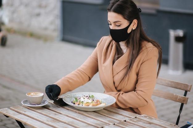 Piękna młoda kobieta jedzenie obiadu w kawiarni na świeżym powietrzu na tarasie. kobieta w czarnej masce ochronnej.