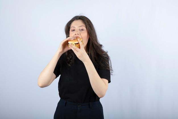 Piękna młoda kobieta jedzenie pysznego burgera wołowego.