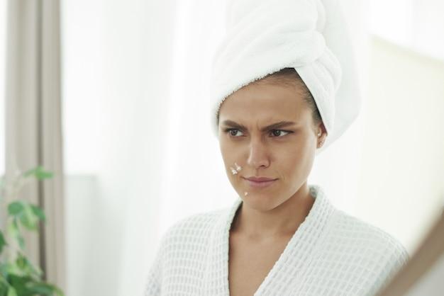 Piękna młoda kobieta jest niezadowolona z pryszczów i nierównej skóry. nakładanie kremu na skórę problematyczną. negatywne emocje.