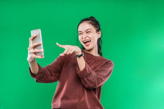 Piękna młoda kobieta jest rozmowa wideo z kimś, wskazując na telefon ze szczęśliwym wyrazem twarzy na zielonym tle