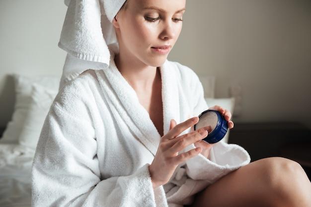 Piękna młoda kobieta jest ubranym białego szlafrok stosuje balsam do ciała