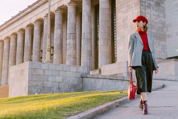 Piękna młoda kobieta jest ubranym czerwoną nakrętkę i torebkę patrzeje daleko od
