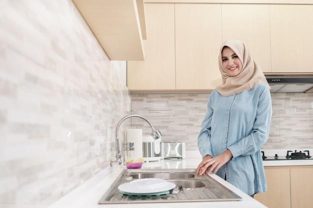 Piękna młoda kobieta jest ubranym hijab myje naczynia
