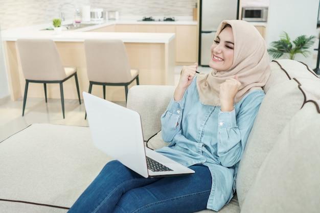 Piękna młoda kobieta jest ubranym hijab ogląda świetnych filmy na kolanach