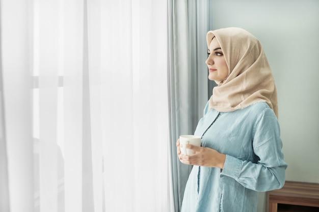 Piękna młoda kobieta jest ubranym hijab pije filiżankę herbata podczas gdy