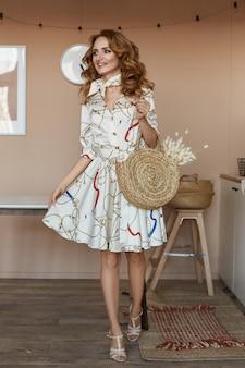 Piękna młoda kobieta jest ubranym krótką lato suknię z kędzierzawym włosy i pozuje w domu w jadalni. koncepcja nowoczesnego mieszkania i wnętrza